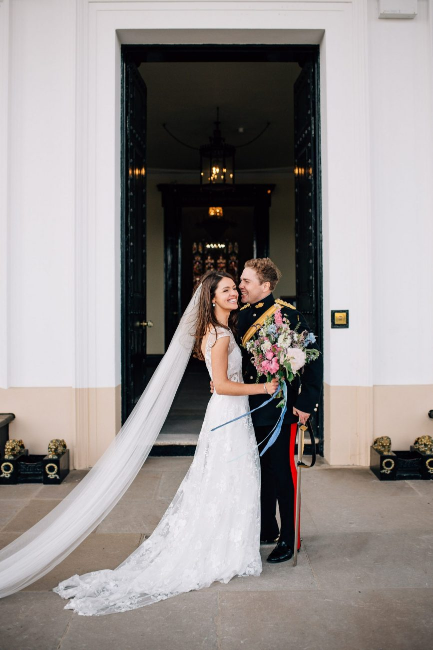 bride and groom laughing and hugging outside of sandhurst military academy